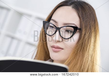 Close up portrait of attractive asian woman in stylish glasses reading book at workplace. She is educating herself. Knowledge concept
