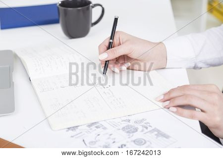 Close up of girl's hand writing in copybook placed on white desktop with coffee cup and other items. Young worker taking notes