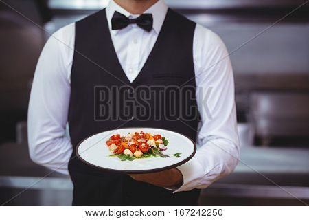 Handsome waiter holding a plate in a restaurant