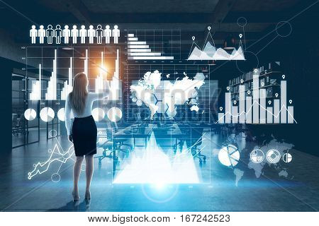 Back view of young businesswoman using hi-tech business panel with charts and diagrams in night office. Trading concept