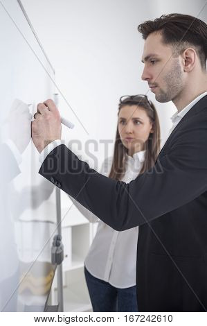 Man Writing At Whiteboard In Office