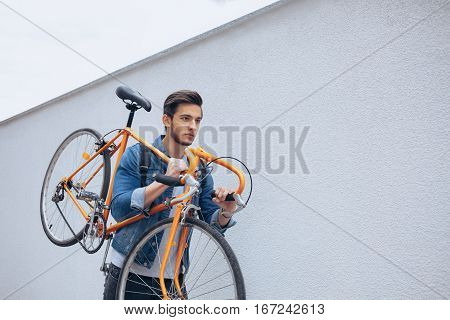 The guy in the blue jeans jacket carrying on his shoulder orange bike. A young serious man has an orange fix bike on his left arm. View from the left side