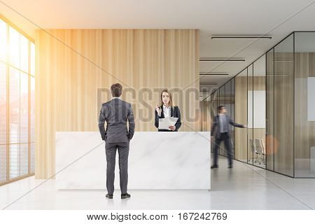 Man standing near a reception desk talking to a receptionist. His colleague is closing a meeting room door. 3d rendering. Mock up. Toned image.