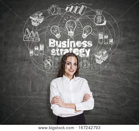 Beautiful smiling european woman on chalkboard background with business sketch. She has chosen her business strategy