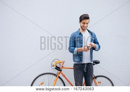 Young student standing near the orange bicycle looking at phone and listening to music. Attractive man with beard is trying to find his the best track during the stop. He is glad of doing this. Wall background