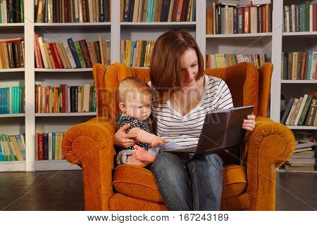 Working mom. Pretty young woman and her child are surfing internet with tablet transformer