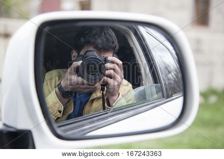 man and photo camera on car in nature