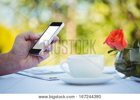 Close up of masculine hands using smartphone at a table