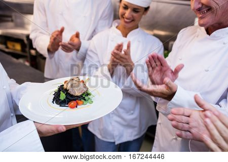Team of chefs applauding in the kitchen