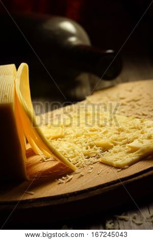 shredded cheese on a wooden board and a bottle of wine. dark still life