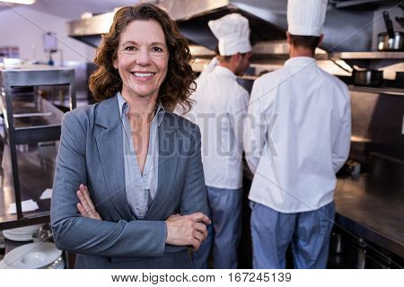 Portrait of happy female restaurant manager standing with arms crossed in commercial kitchen