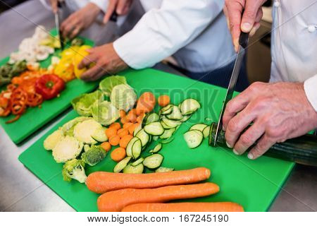 Close-up of chefs chopping vegetables on chopping board in the kitchen
