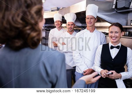 Female restaurant manager briefing to his kitchen staff in the commercial kitchen