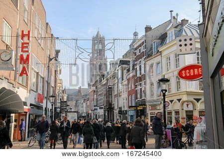 Utrecht the Netherlands - February 13 2016: People walking in historic city centre. View to Dom Tower of the St. Martins Cathedral