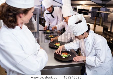 Head chef overlooking other chef decorating dish in the kitchen