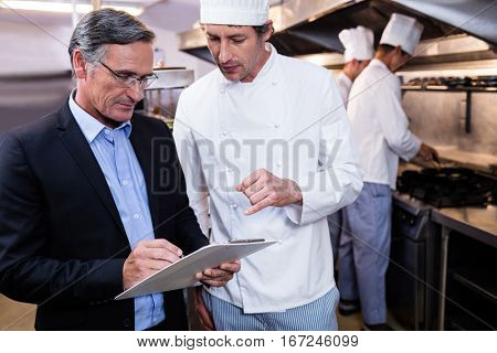 Male restaurant manager writing on clipboard while interacting to head chef in commercial kitchen