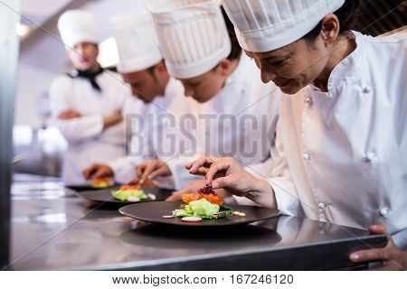 Chef decorating a food plate in the commercial kitchen