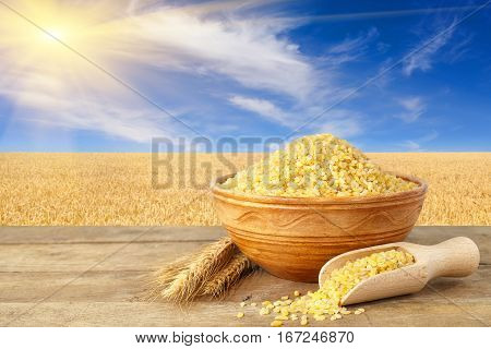 Bulgur or couscous in bowl. Bulgur in ceramic bowl and ears of wheat on table with field of wheat on the background. Ripe wheat field, blue sky with beautiful clouds and sun
