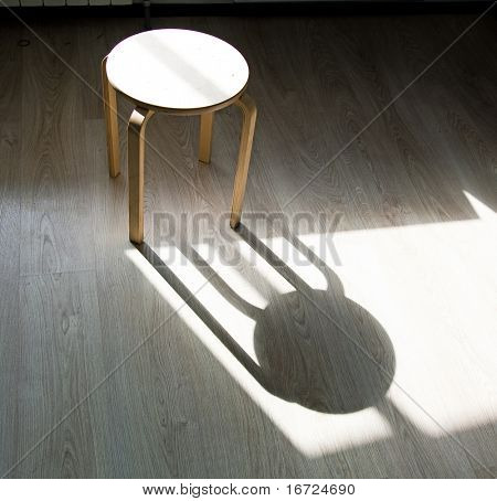 the  stool and shadow on the parquet floor