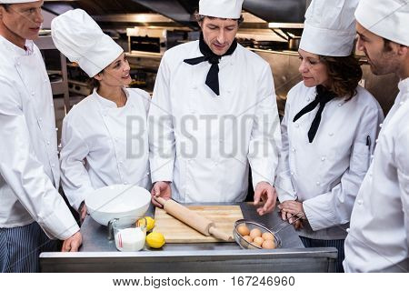 Head chef in commercial kitchen teaching his team to prepare a dough