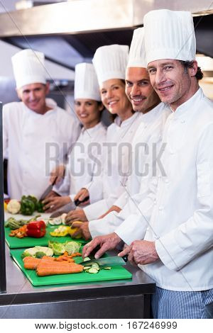 Team of chefs smiling at camera while chopping vegetables on the chopping board in the kitchen