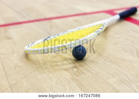 Closeup of a squash racket and ball on the wooden background. Racquetball equipment. Squash ball between squash racket and floor on the court. Photo with selective focus