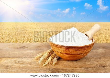 wheat flour in ceramic bowl. Ears of wheat and flour in bowl on table with field on the  background. Ripe wheat field, blue sky, sun. Photo with copy space area for a text