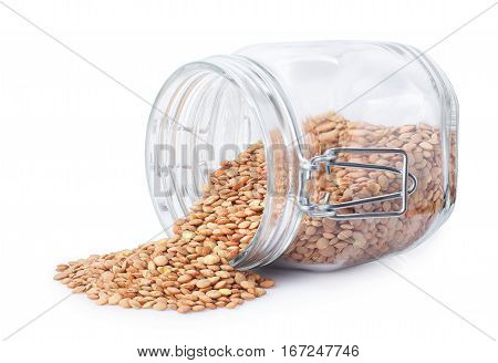 lentil in a glass jar isolated on white background. Uncooked dry lentil scattered out of glass container. Green lentil spilling out of glass jar