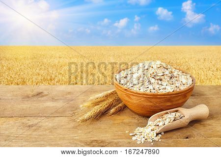 Oat flakes in bowl. Ears of oats and oatmeal in bowl on table with field on the background. Agriculture and harvest concept. Ripe wheat field, blue sky, sun. Uncooked porridge