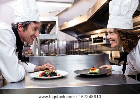 Two smiling chefs leaning on kitchen counter with meal plates