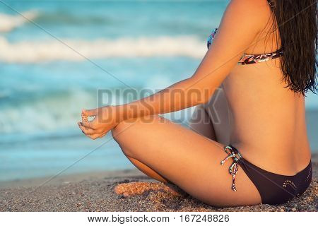 closeup young woman in swimwear sitting on the sunset beach. Girl meditating on the beach. Girl relaxing in lotus pose in calm zen moment in the ocean water during yoga holidays resort retreat