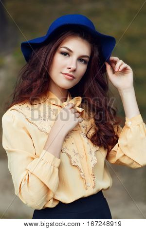Outdoor closeup fashion portrait of sensual young stylish lady wearing trendy hat and blouse with bow. Fashion woman with curly hair and floppy hat. Young beautiful brunette girl with brown eyes