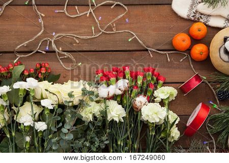 New Year background of various winter flowers with lightened candles and Christmas lights