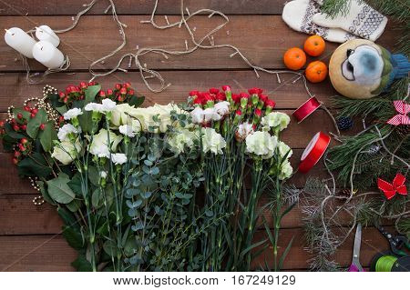 Various winter flowers with lightened candles and Christmas lights on the wooden background