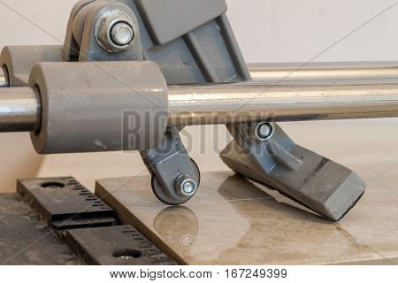 Ceramic tiles and tools for tiler. Floor tiles installation. Home improvement renovation - ceramic tile cutting tool.