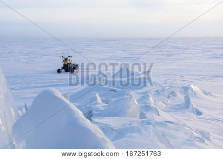 Snowmobile standing on the frozen lake, pieces of ice and frost.