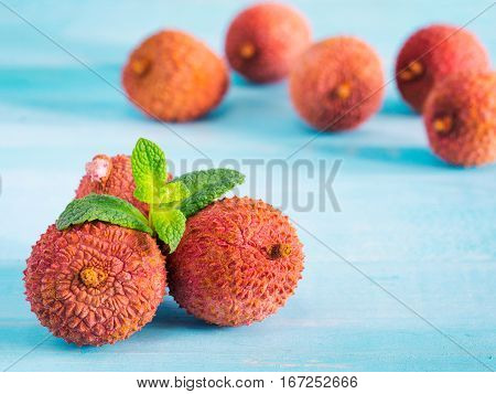 lichee fruit on turquoise wooden background close up
