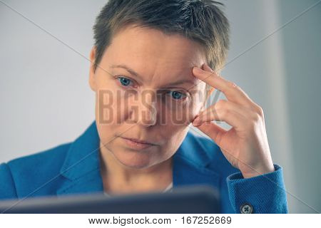Disappointed businesswoman looking at business results on laptop screen in the office
