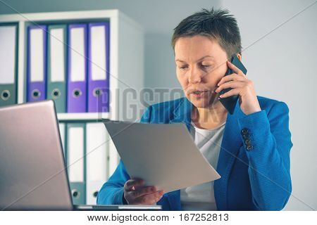 Businesswoman negotiating contract agreement details over mobile phone with business partners while sitting at the office desk