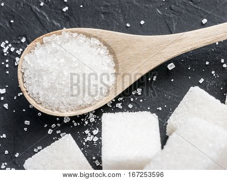 Granulated sugar in wooden spoon close up. Background of sugar cubes and sugar in spoon. White sugar on black background.