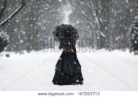 Mysterious lonely woman in Victorian dress departing into the distance