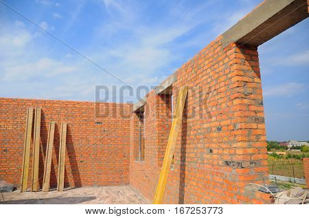 Interior of a Unfinished Red Brick House Walls under Construction without Roofing. Closeup on Attic Windows Hole Frame Construction Outdoors