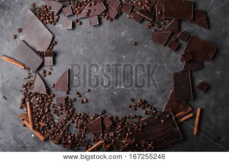 Coffee beans and dark chocolate. Chocolate bar . Background with chocolate. Coffee beans. Cinnamon sticks and star anise. A large bar of chocolate on gray abstract background.