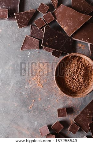 Chocolate chunks and cocoa powder. Chocolate bar pieces. A large bar of chocolate on gray abstract background. Background with chocolate. Slices of chocolate Sweet food photo concept. Copyspace