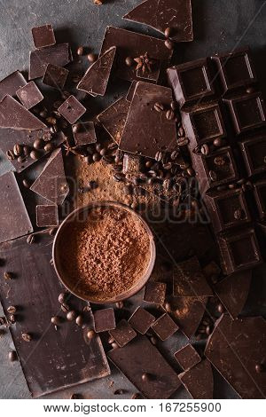 Chocolate chunks and cocoa powder. Coffee beans Chocolate bar pieces. Large bar of chocolate on gray abstract background. Background with chocolate. Slices of chocolate. Sweet food photo concept.