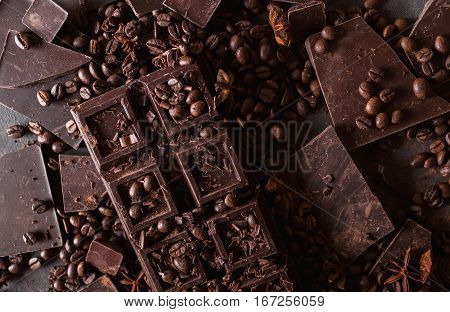 Chocolate coffee beans. and cocoa powder. Chocolate bar pieces. dark chocolate background. A large bar of chocolate on gray abstract background. Background with chocolate. Slices of chocolate
