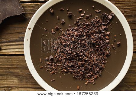 Slices of chocolate on a plate on a wooden background. Chocolate. Background with chocolate