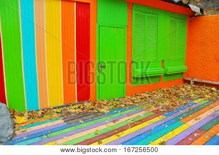 Colorful house. Bright colorful wall facade with green door and windows