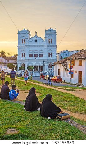 GALLE SRI LANKA - DECEMBER 3 2016: People sit on the grass and enjoy the sunset view on Meera Mosque on December 3 in Galle.