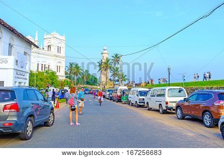 GALLE SRI LANKA - DECEMBER 3 2016: The tourists walk along the Rampart Street to its main landmarks - Meera Mosque and the old lighthouse on December 3 in Galle.